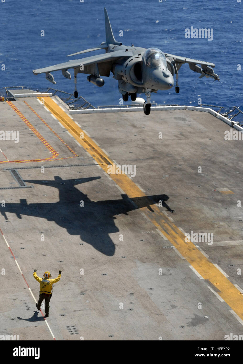 Crew members guide an AV-8B Harrier to the flight deck of the amphibious assault ship USS Peleliu. Peleliu is on Stock Photo