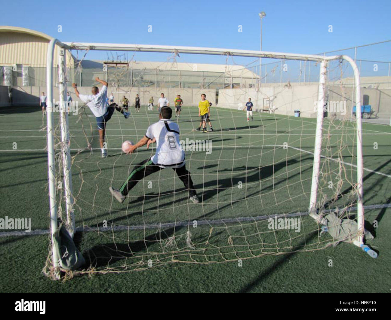 Afghan Air Force Thunder Lab officers play football against their American mentors for their morning physical training - Stock Image