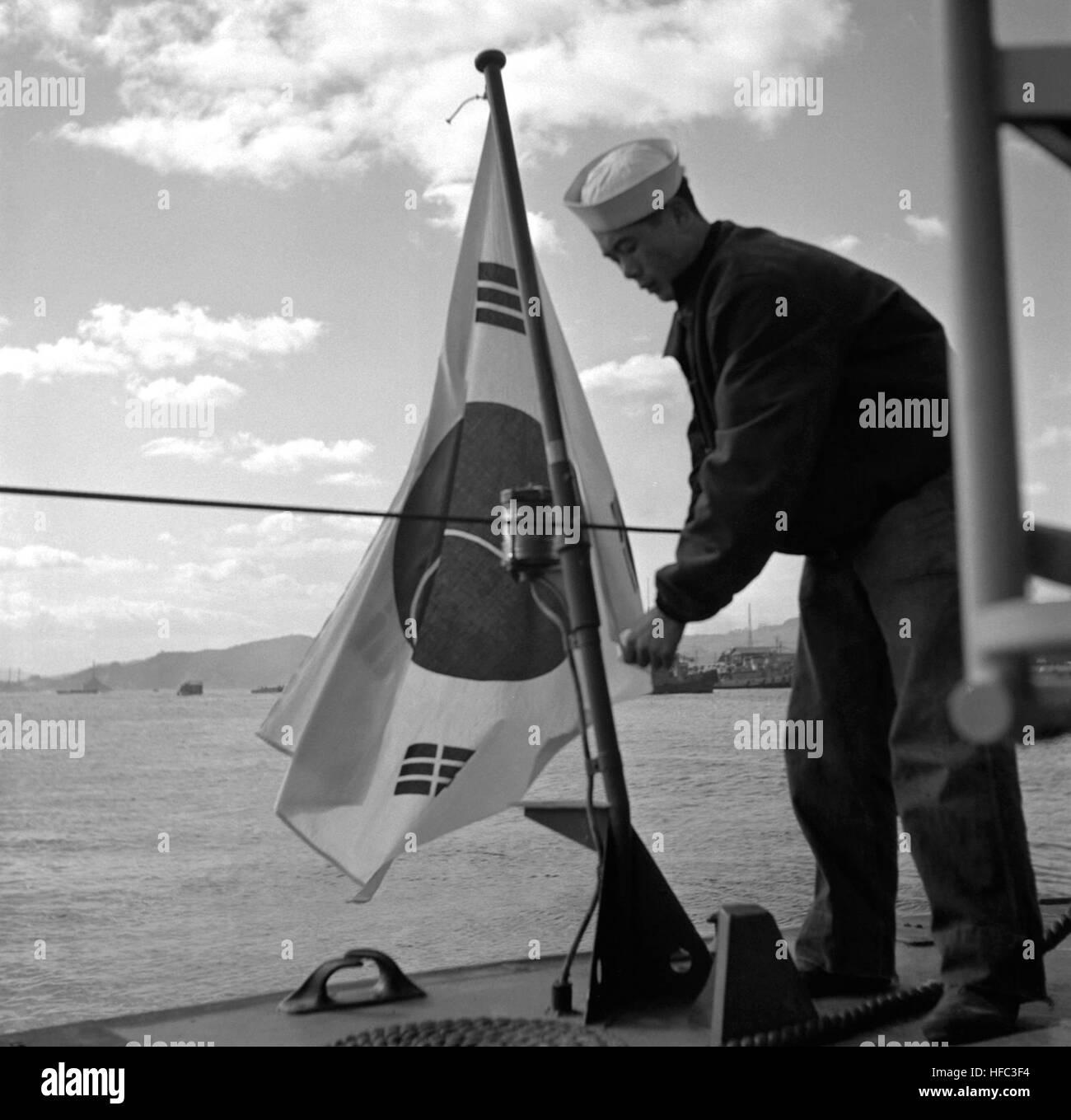 ROK sailor raising Korean flag on stearn of PT boat after transfer from U.S. Navy at Sasebo, Japan. NARA FILE #: Stock Photo