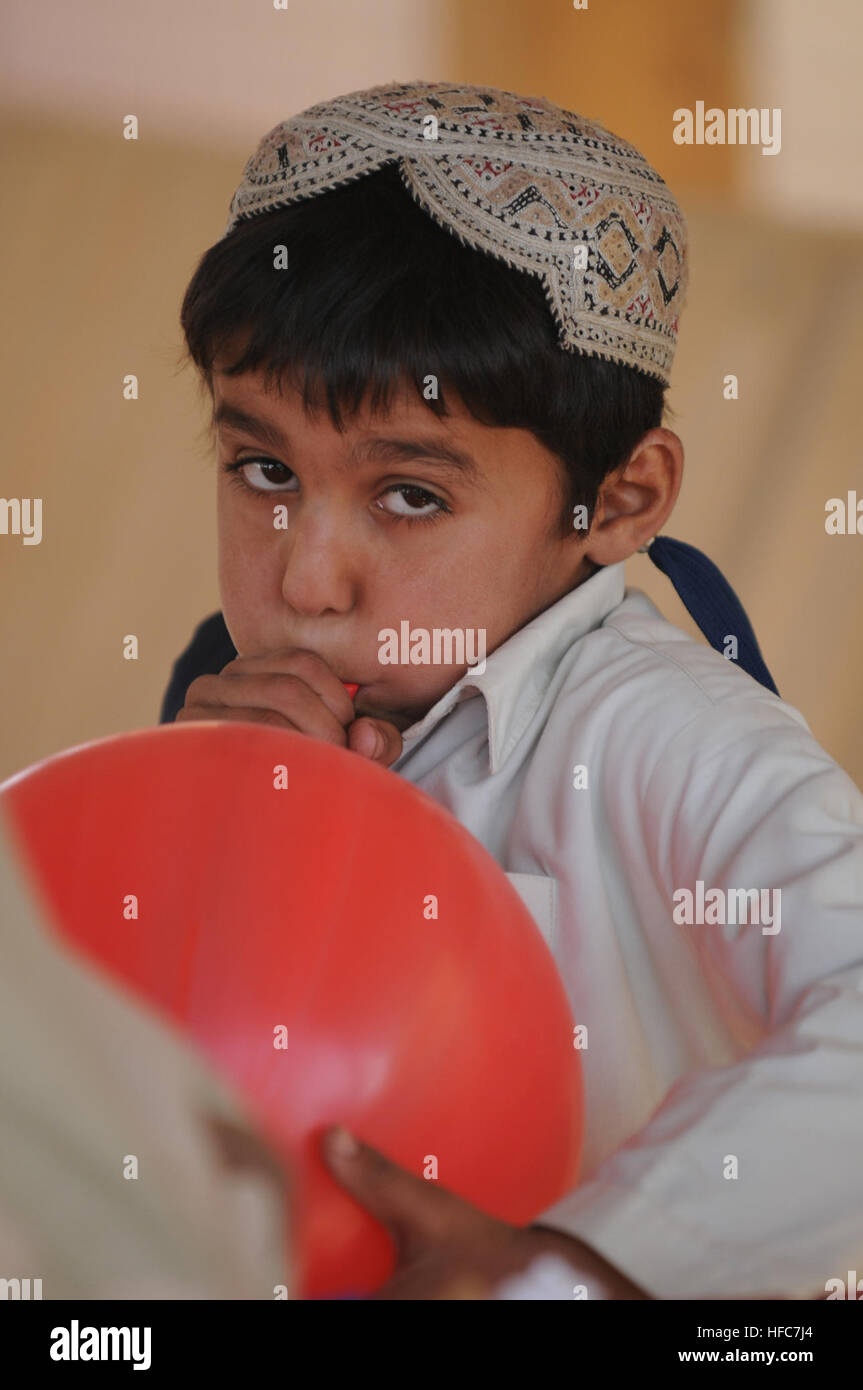 An Afghan boy blows up a balloon during the hour of crafts