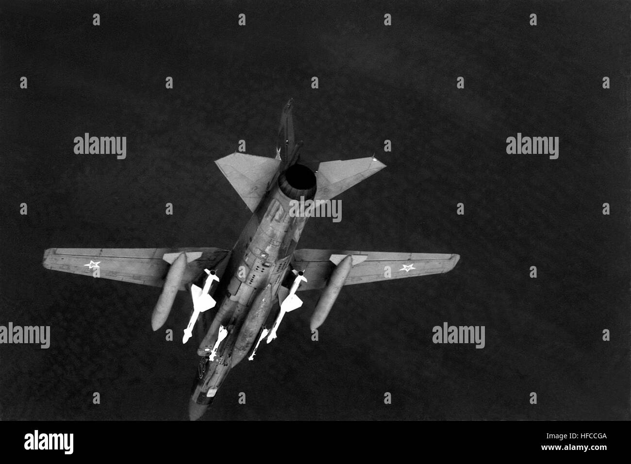 An air-to-air underside view of a Soviet MiG-23 Flogger aircraft.  The aircraft is armed with AA-7 Apex missiles - Stock Image