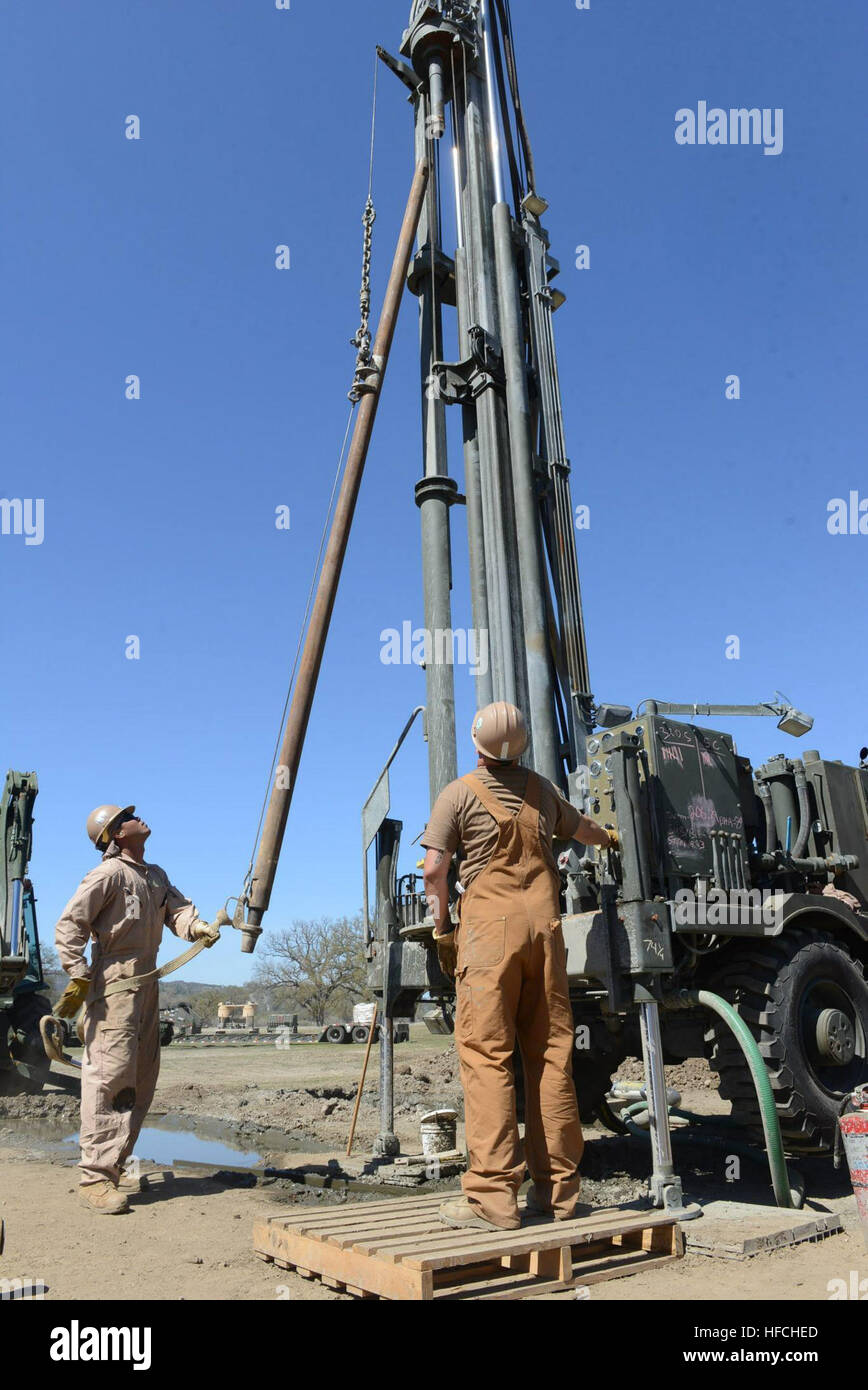 Members of Naval Mobile Construction Battalion 4's water well team attach drill-steel to an International Standards - Stock Image