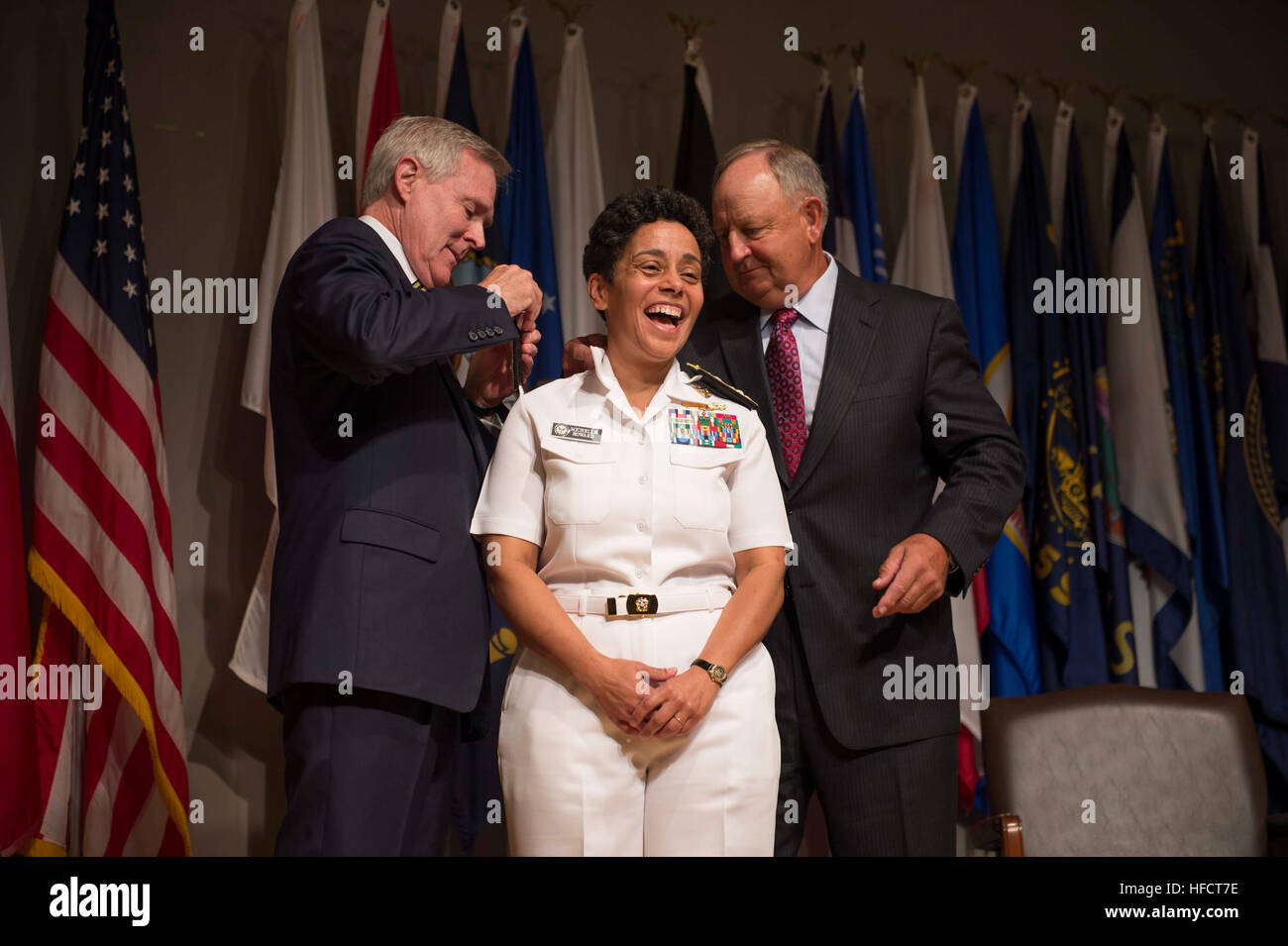 Secretary of the Navy Ray Mabus, left, and Wayne Cowles, husband of Adm. Michelle Howard, put four-star shoulder Stock Photo