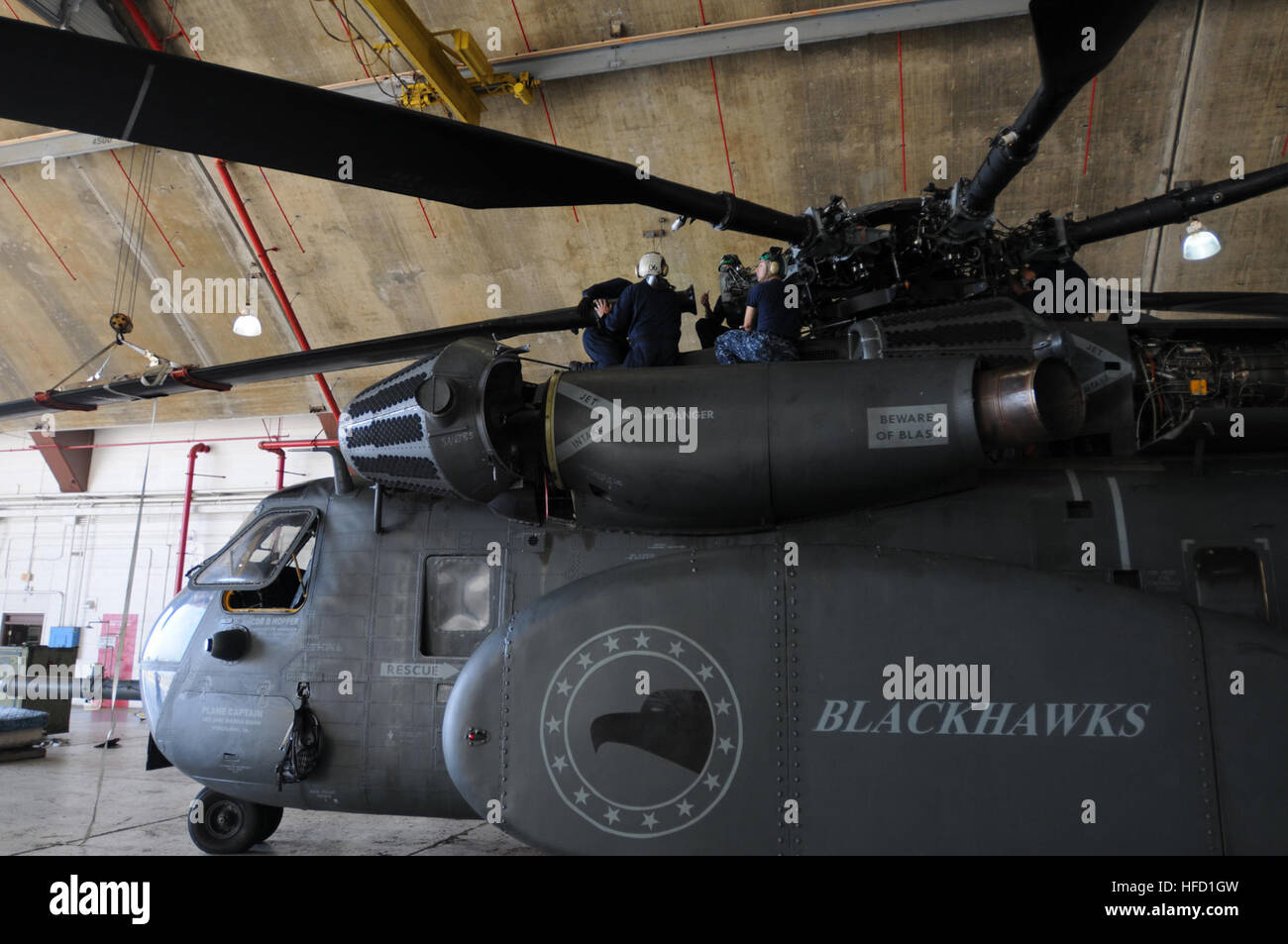 Crewmembers assigned to Helicopter Mine Squadron 15, attach a rotor blade to the rotor head of a MH-53E Sea Dragon Stock Photo