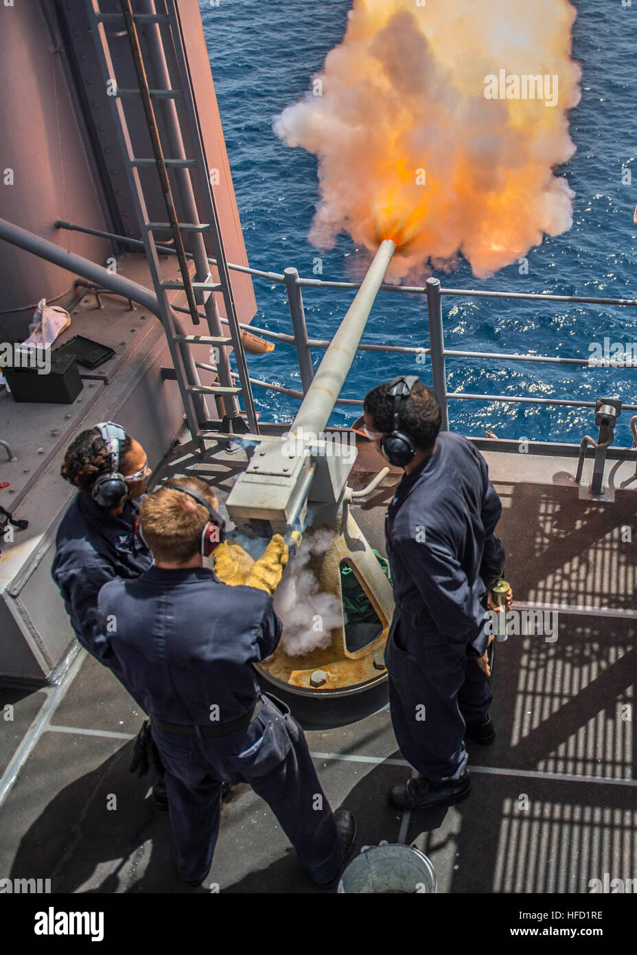 150627-N-MD297-069  GULF OF ADEN (JUNE 27, 2015) Gunner's mates fire a 40mm saluting battery from the vulture's - Stock Image