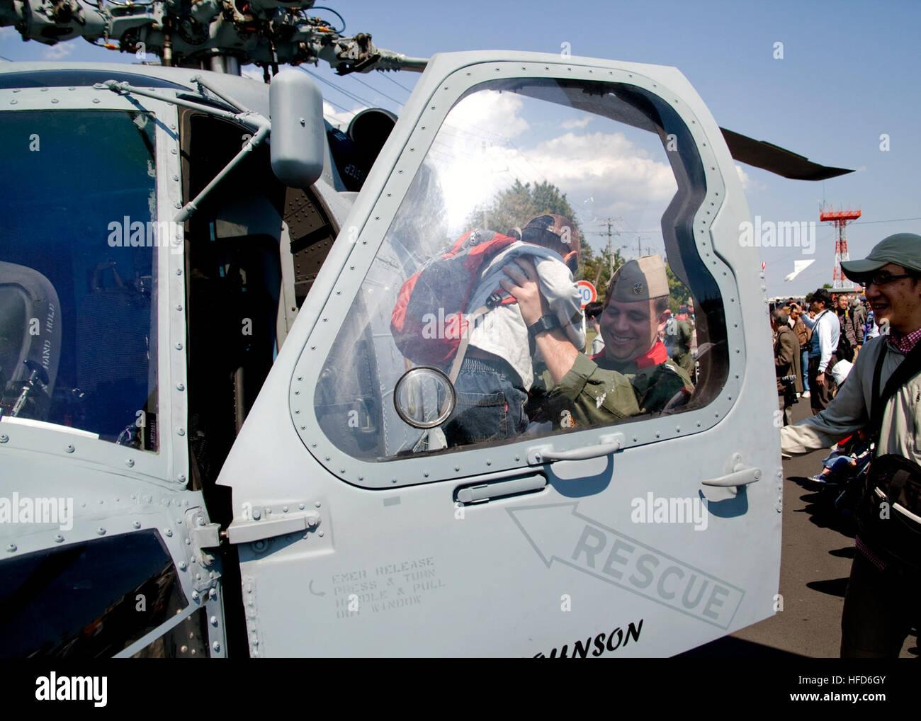 AYASE, Japan (April 27, 2013) Lt. James Walsh, of Helicopter Maritime Strike Squadron (HSM) 51, helps a japanese - Stock Image