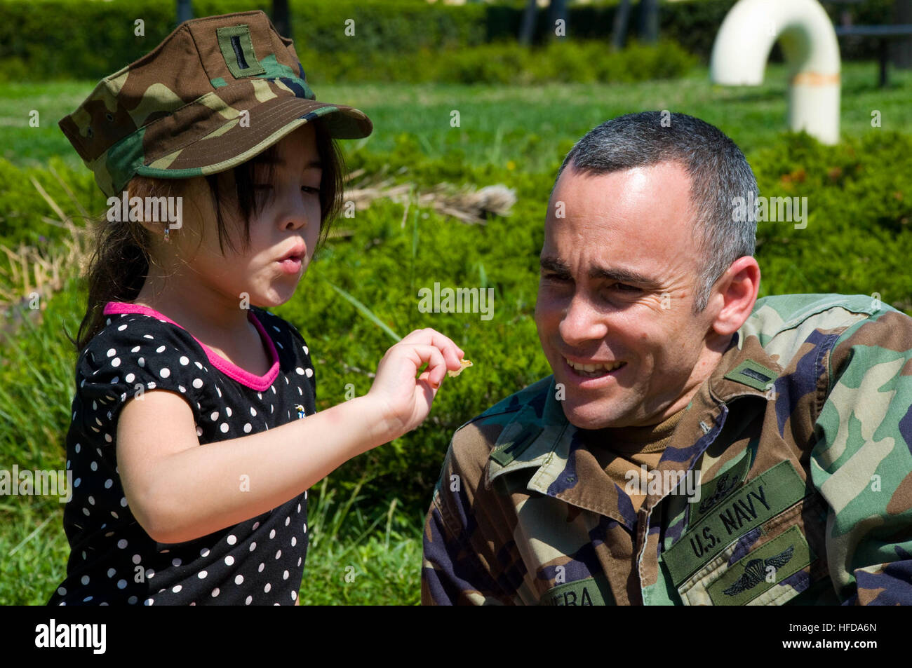 Lt. j.g. Angel Olivera spends time with his daughter during a 'Month of the Military Child' event at Naval - Stock Image