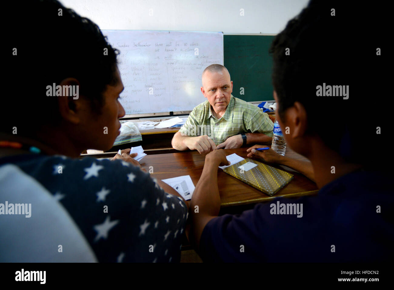 Commander of the 30th Naval Construction Regiment Navy Capt. Rod Moore helps two Timorese college student attending Stock Photo