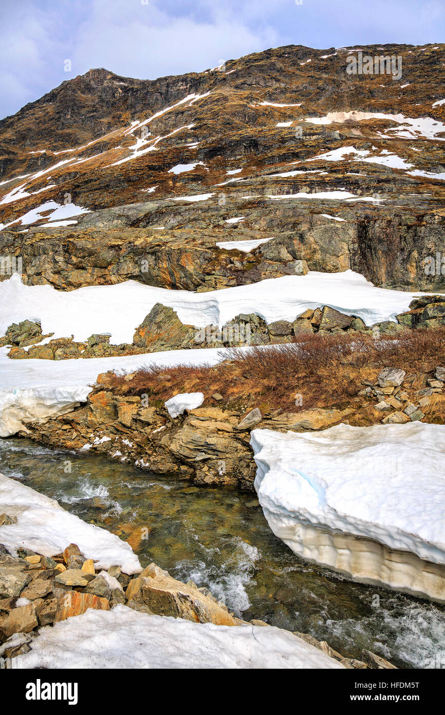Thawing snow revealing the rocky landscape at Jotunheimen National Park, Norway - Stock Image