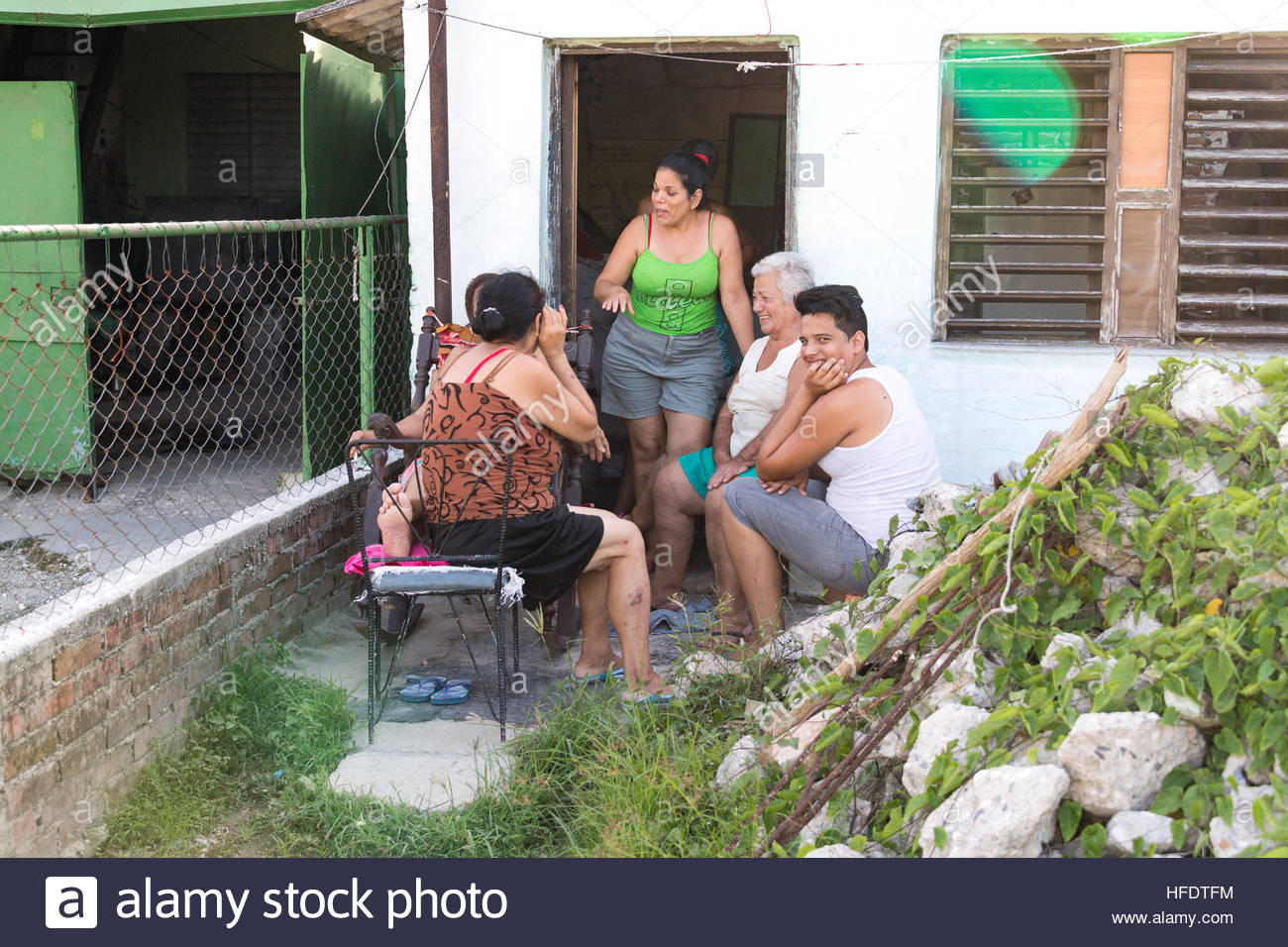 Cuban everyday lifestyle: A Cuban family or neighbors sitting together and talking outside their doorstep. - Stock Image
