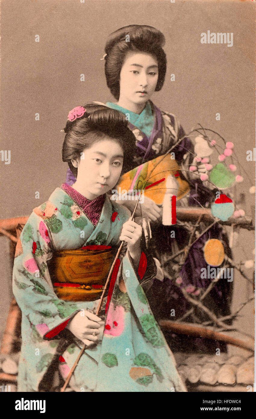Circa 1900 sepia Japanese postcard. Women, geisha sitting golding sprig . Hand-coloured. - Stock Image