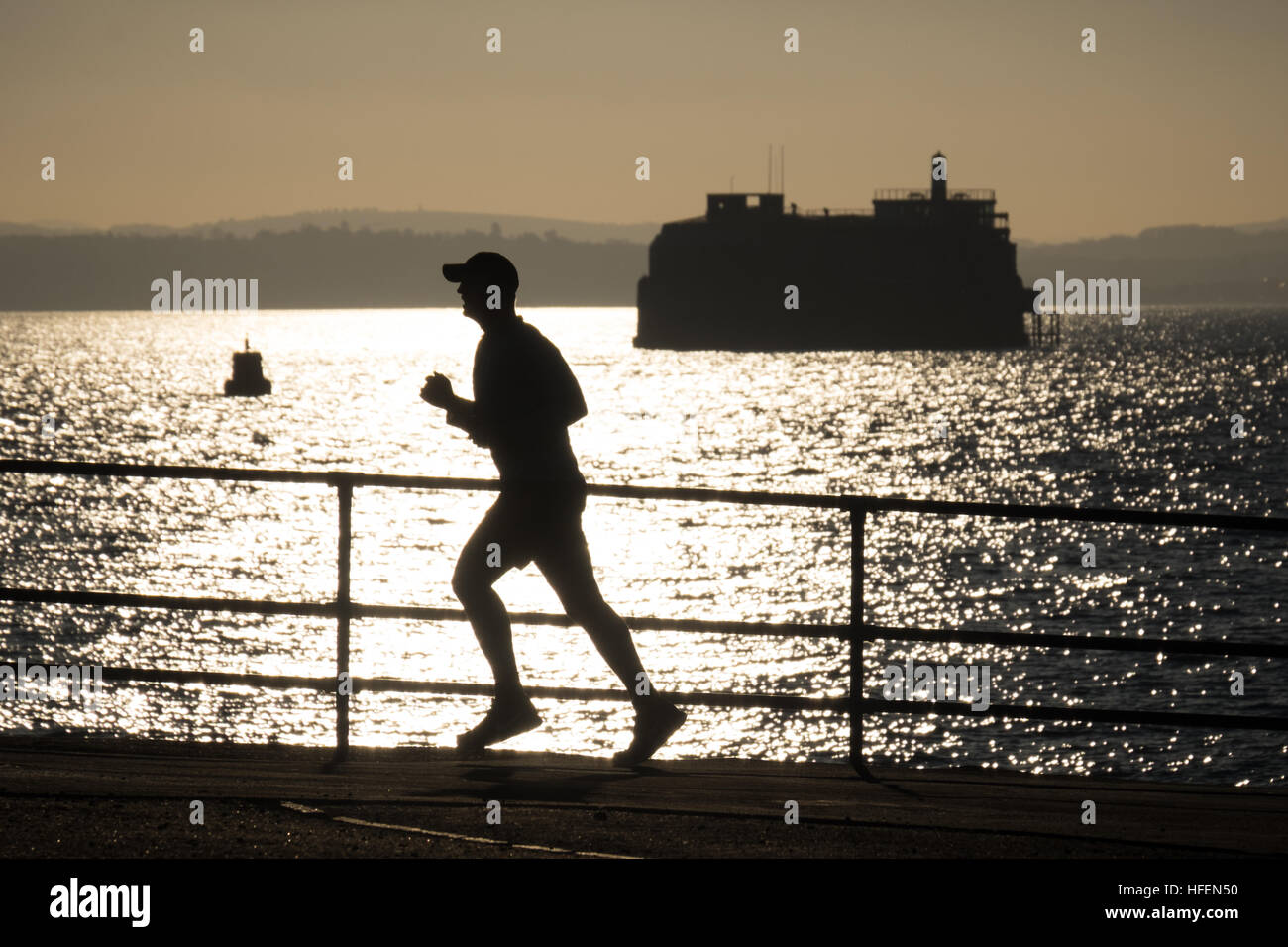 A runner enjoying the sunny weather between Christmas and New Year on Southsea Promenade - Stock Image