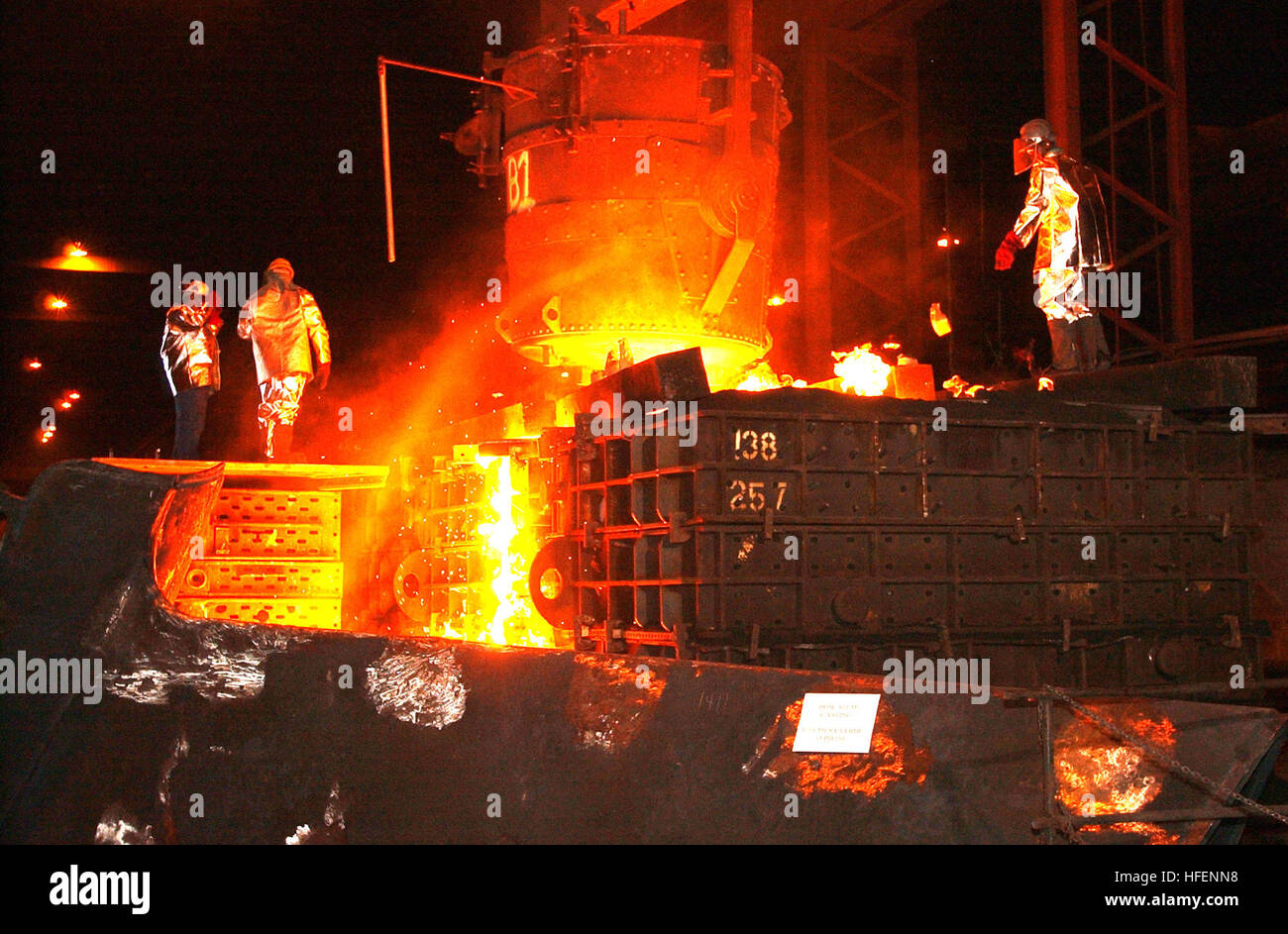 030909-N-9954T-005 Amite, La. (Sept. 9, 2003) -- Foundry workers pour molten steel into a mold to form the bow stem Stock Photo