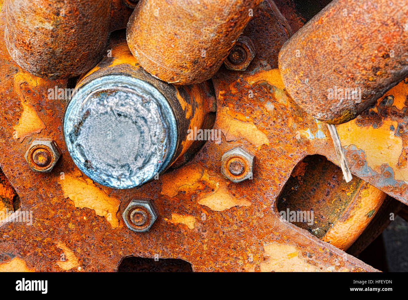 Rusted, vintage, antique, wheel hub in salvage  yard.  Spokes, bolts, and bearings. - Stock Image