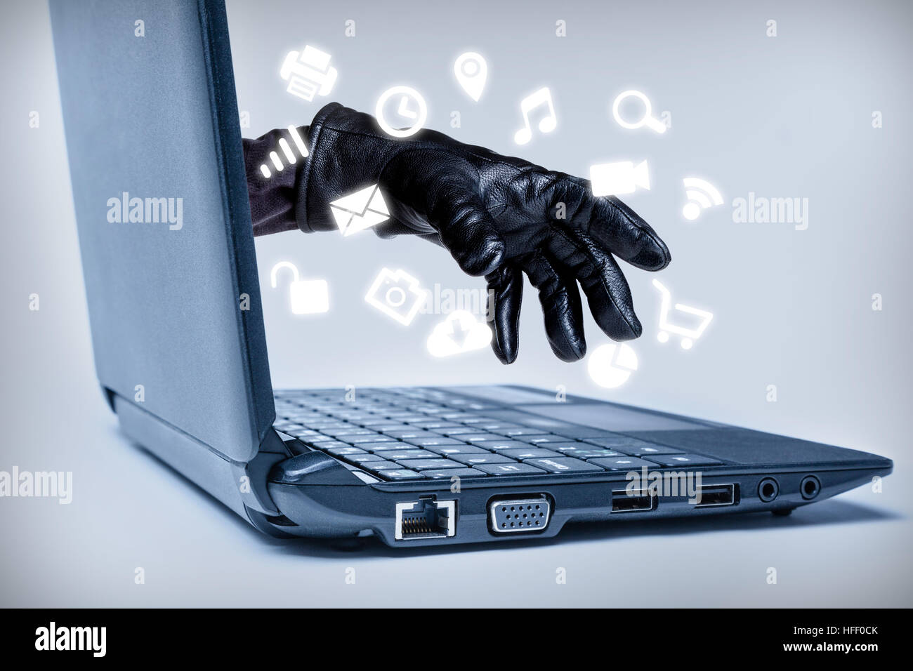 A gloved hand reaching out through a laptop with common media icons flowing, signifying a cybercrime or Internet - Stock Image