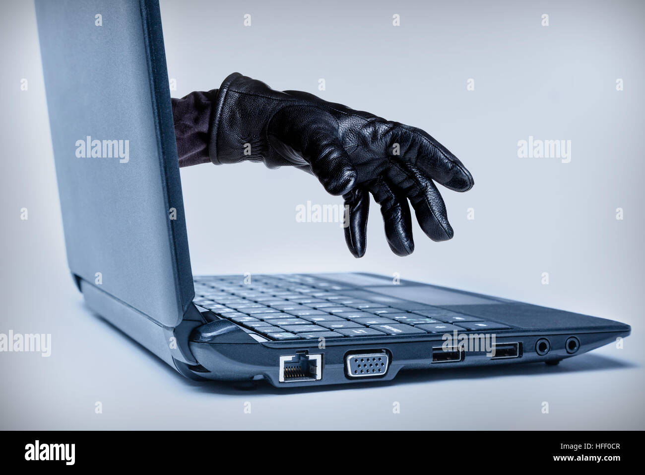 A gloved hand reaching out through a laptop, signifying a cybercrime or Internet theft while using Internet media. - Stock Image