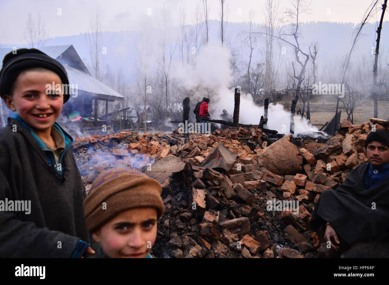 Children's looking at the devastation in which 32 structures were gutted atTandu Mohalla in Wadder Payeen of - Stock Image