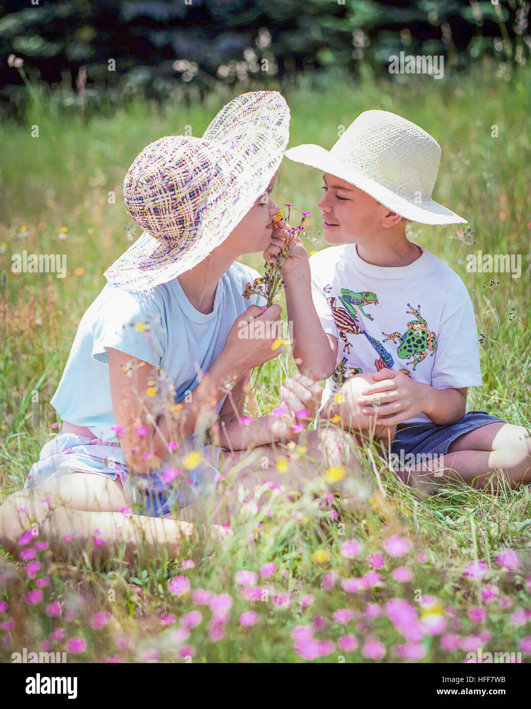 Happy children, a boy and girl, in straw hats sit in a field smelling wildflowers. - Stock Image