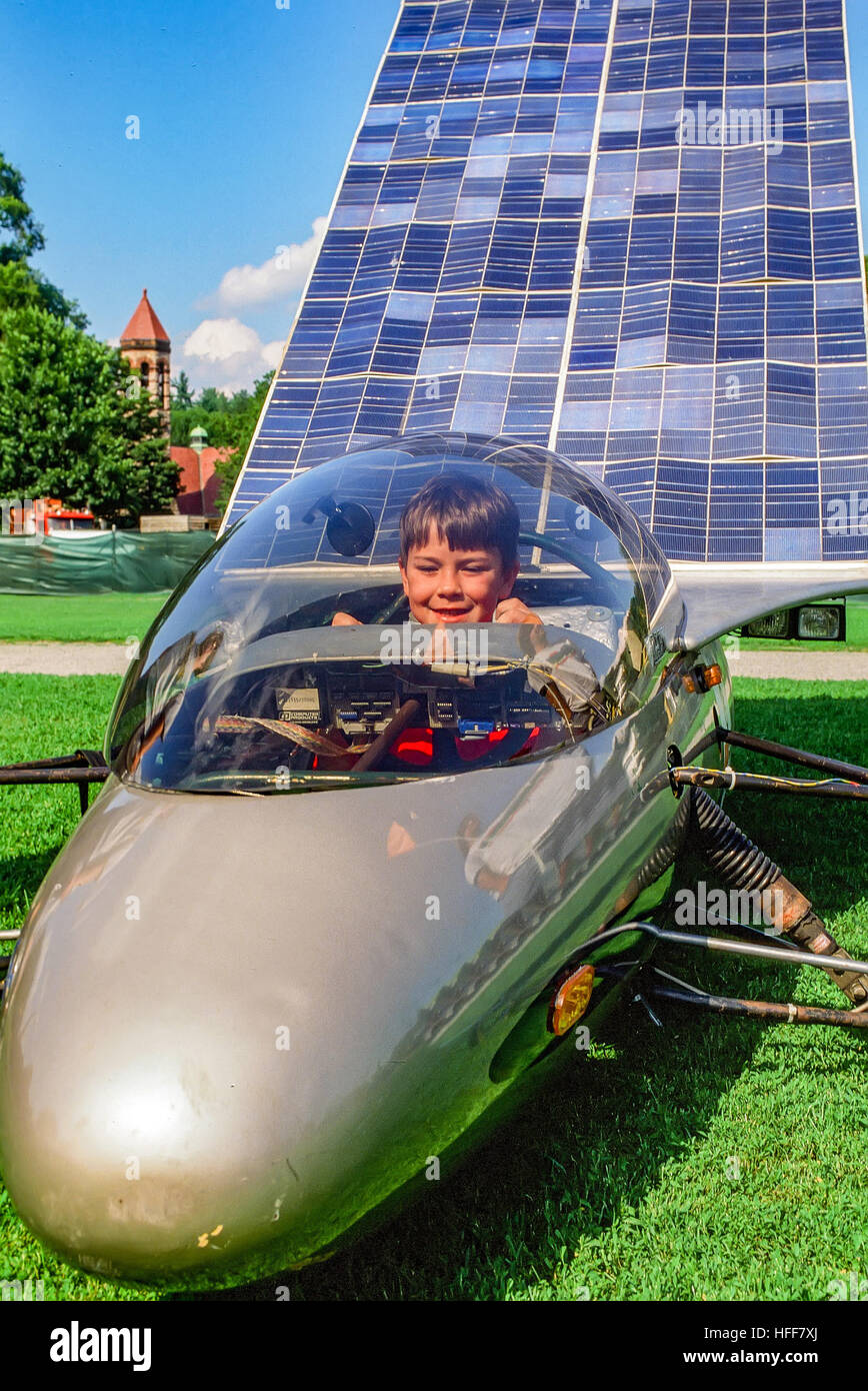 A young boy sits in the cockpit of a solar powered car on display at a solar technology show. Stock Photo