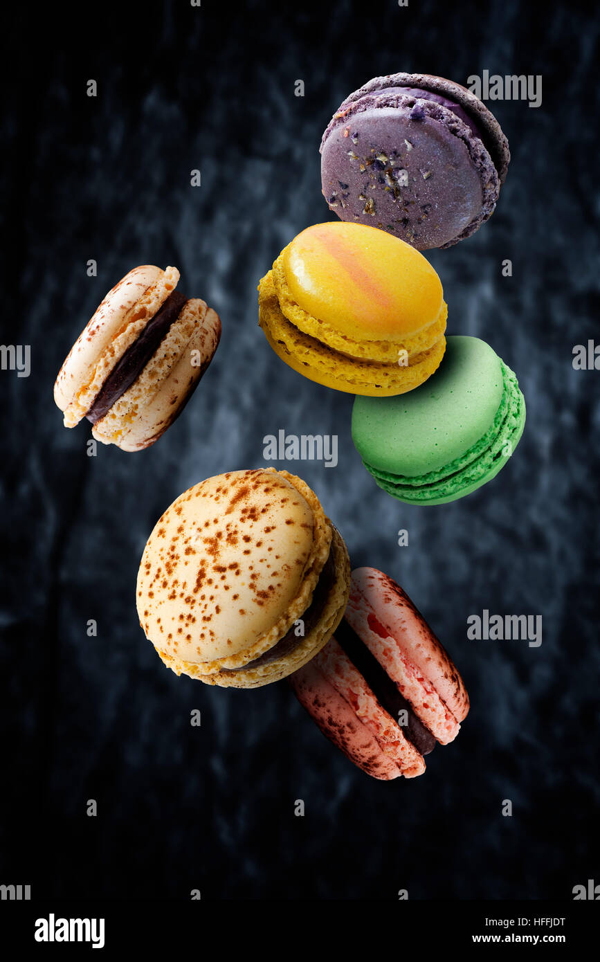 Assorted multi flavored macaroons floating against dark background - Stock Image