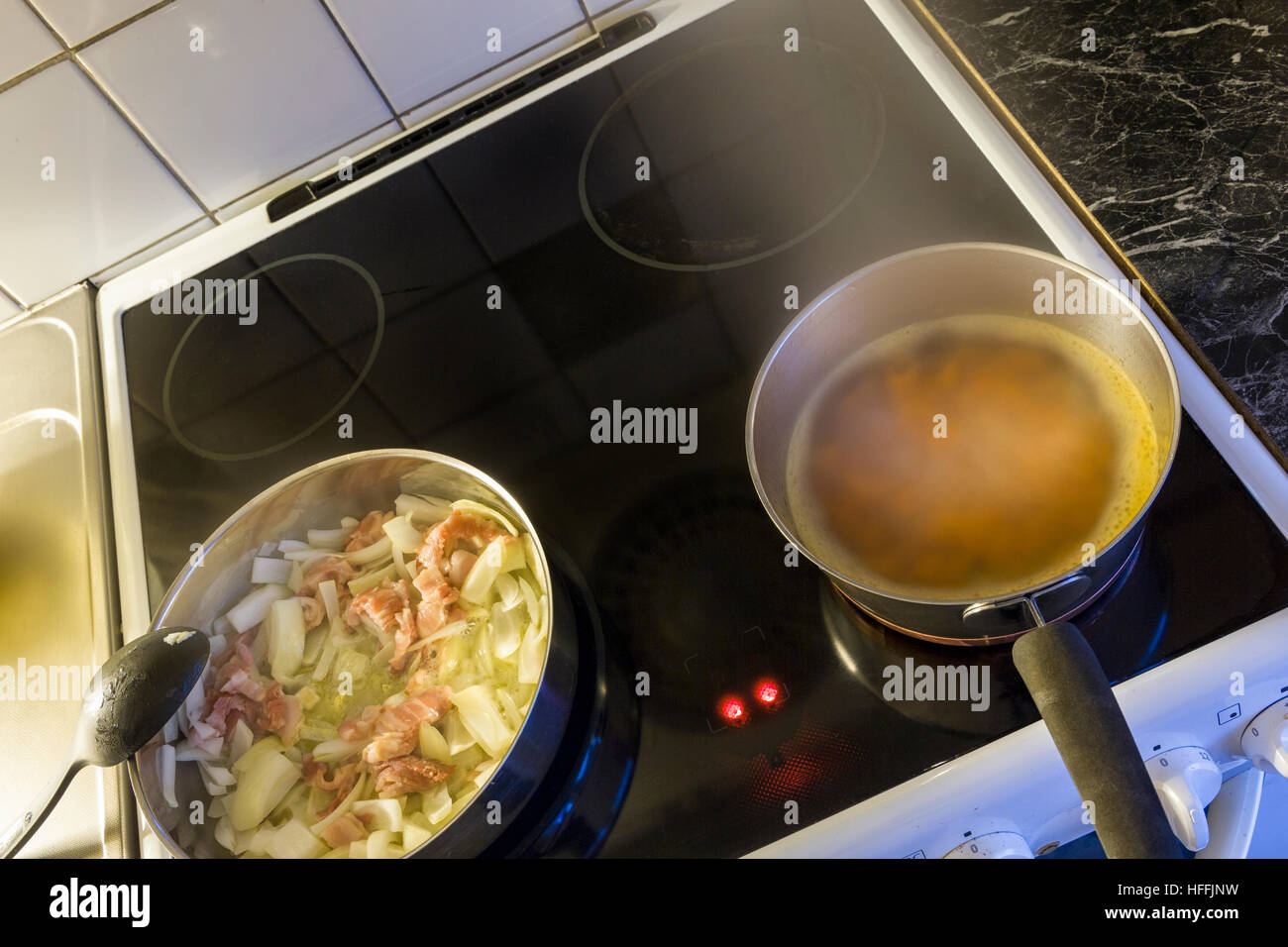 Dinner meal being prepared and cooked on kitchen stove  Model Release: No.  Property Release: No. - Stock Image