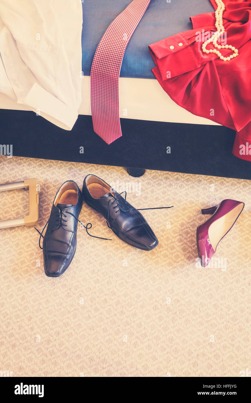 Retro toned shoes and clothes in disorder in a hotel room, copy space. - Stock Image