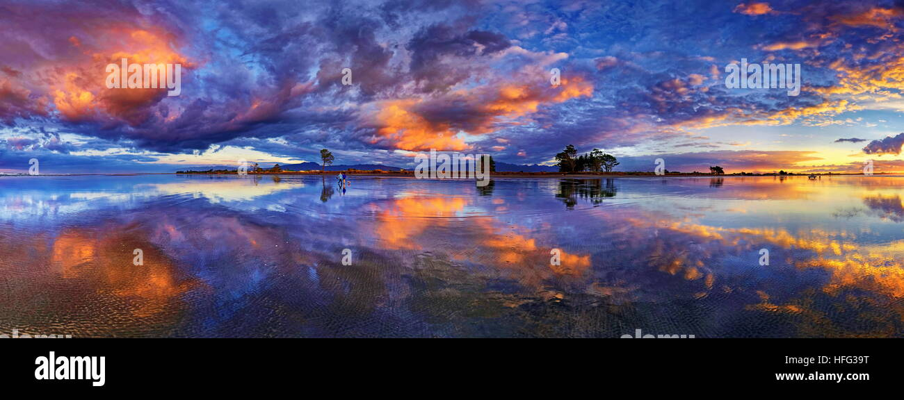 Panorama with glorious sunset at Carters Beach, cloudy sky, Water Reflection, Westport, West Coast, Southland, New - Stock Image