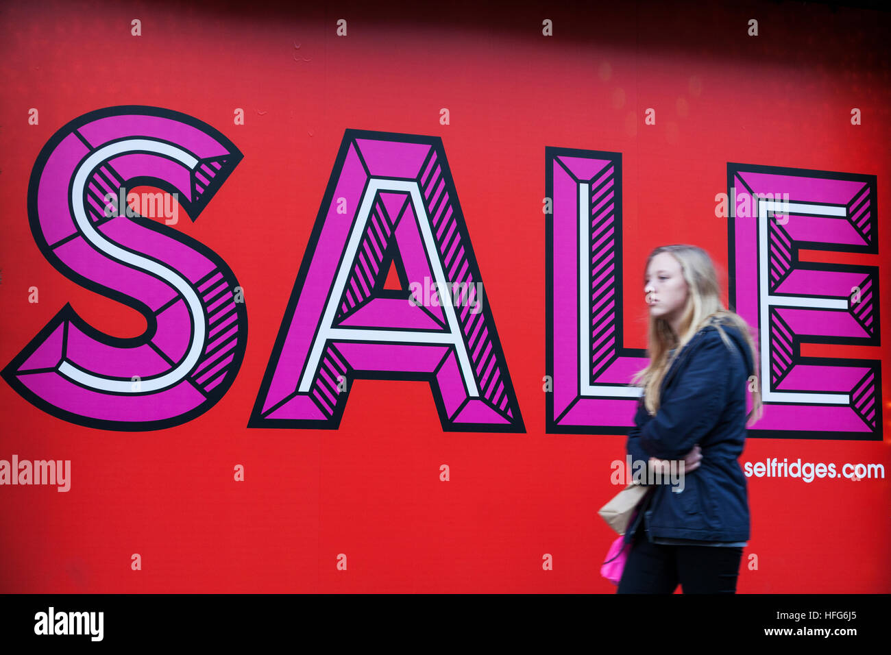 Young female shopper walks past sale sign on Oxford Street, London - Stock Image