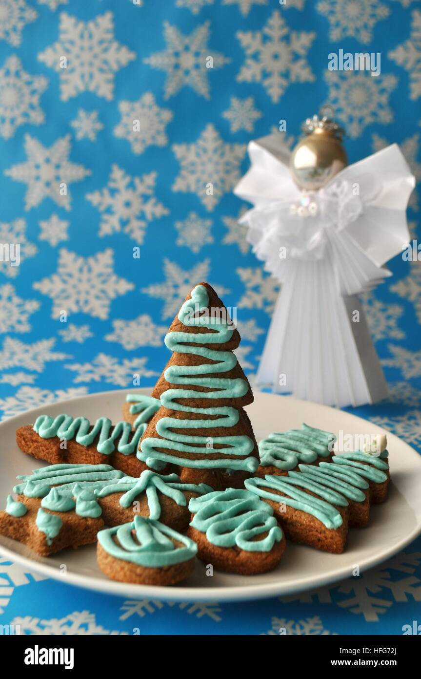 Close up of various festive Christmas holiday sweets, treats and cookies on blue background with white snow flakes - Stock Image