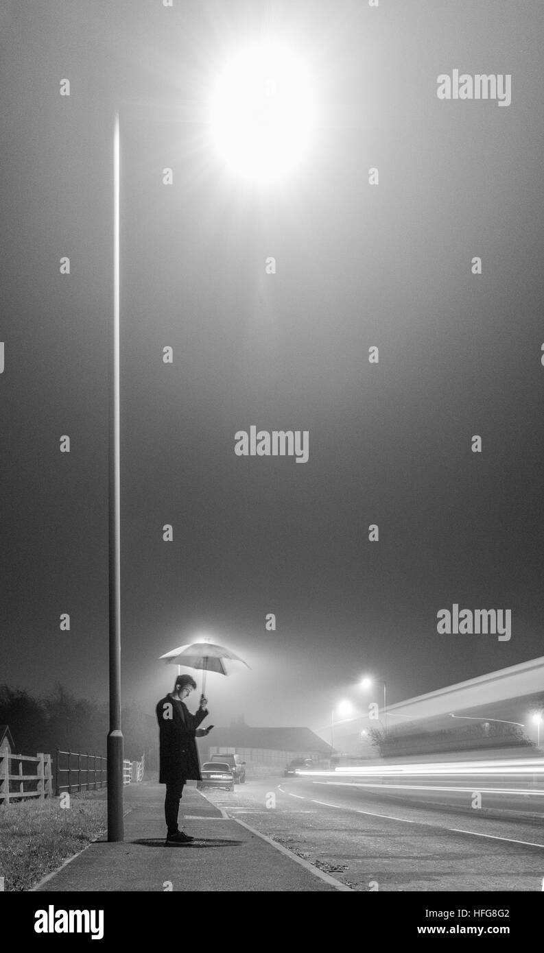 young man under street lamp with umbrella on foggy evening - Stock Image