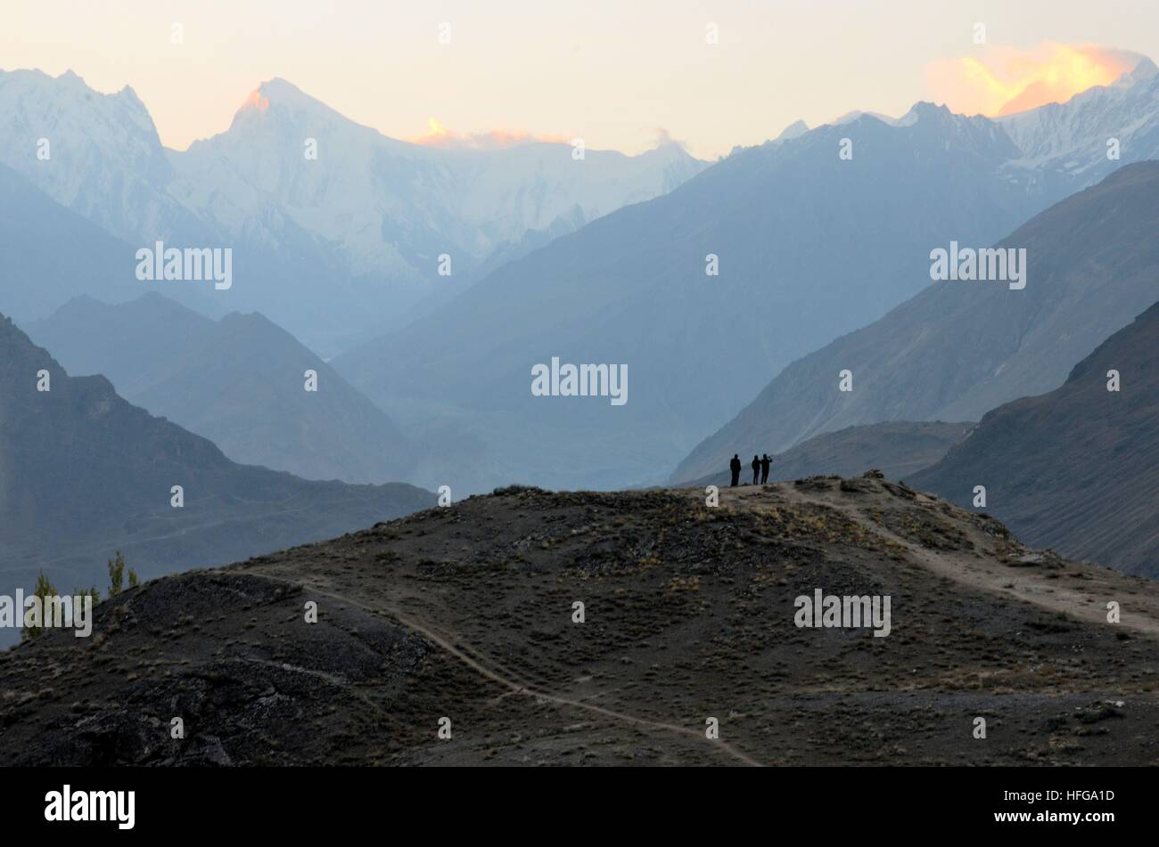 Men on mountain peak watch sunrise among the Karakoram mountains in Duiker Plateau Hunza Valley Pakistan - Stock Image