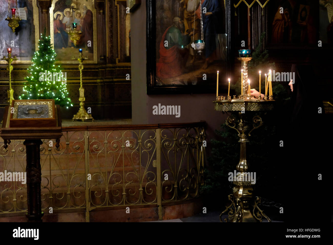 A Russian Orthodox nun lighting candles inside of the Holy Trinity Cathedral of the Russian Ecclesiastical Mission - Stock Image