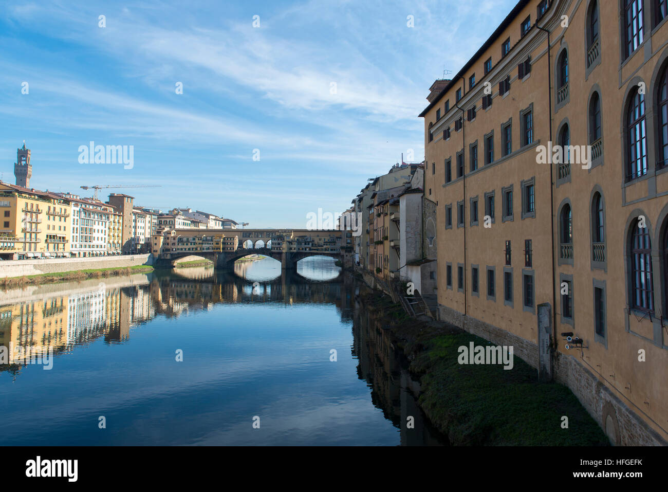 View of Arno river embankment with architecture and Ponte Vecchio bridge reflected on water - Stock Image