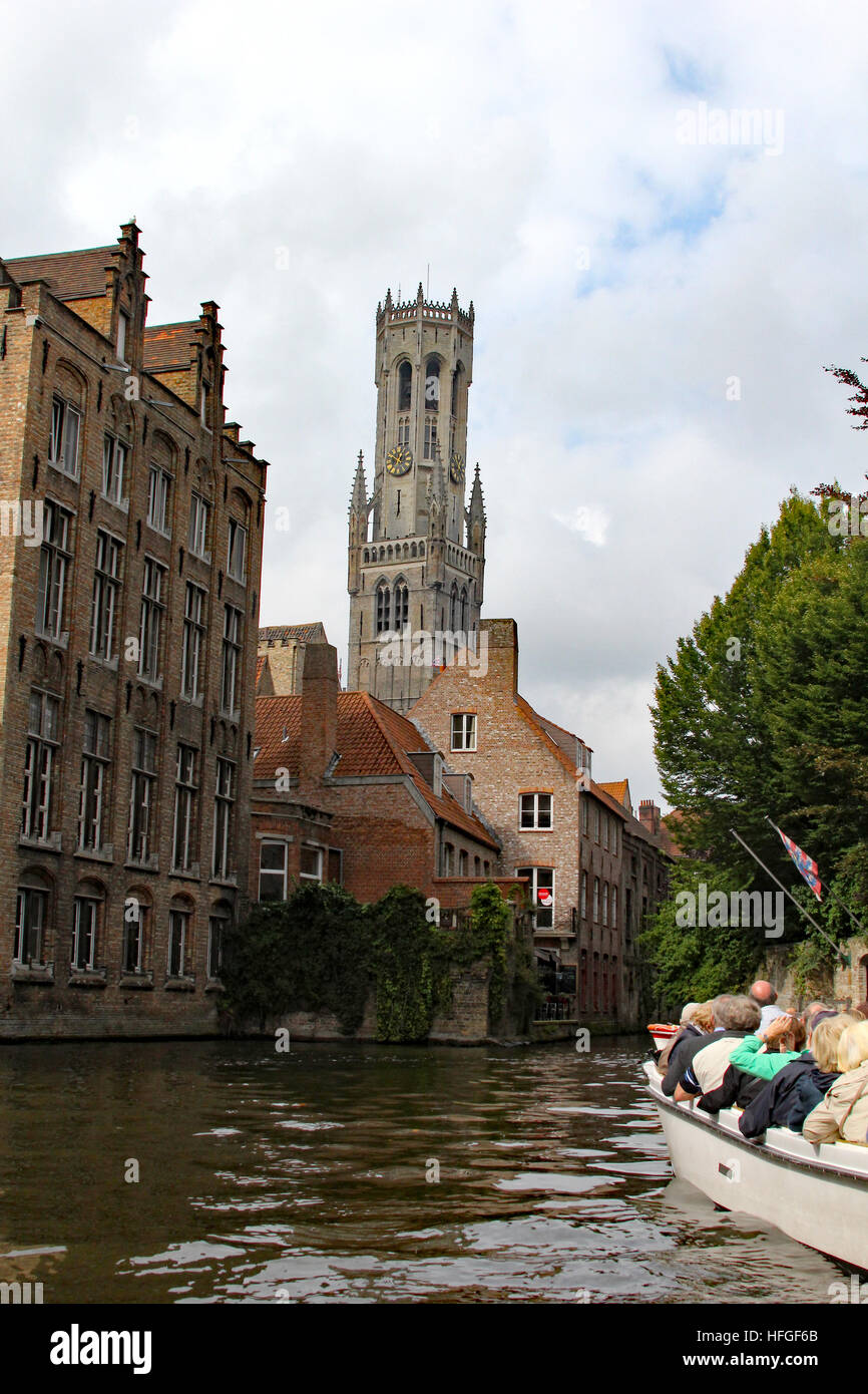 The canals of Bruges offer charm and a unique vantage to view the city, and tour boats ply their way through the Stock Photo