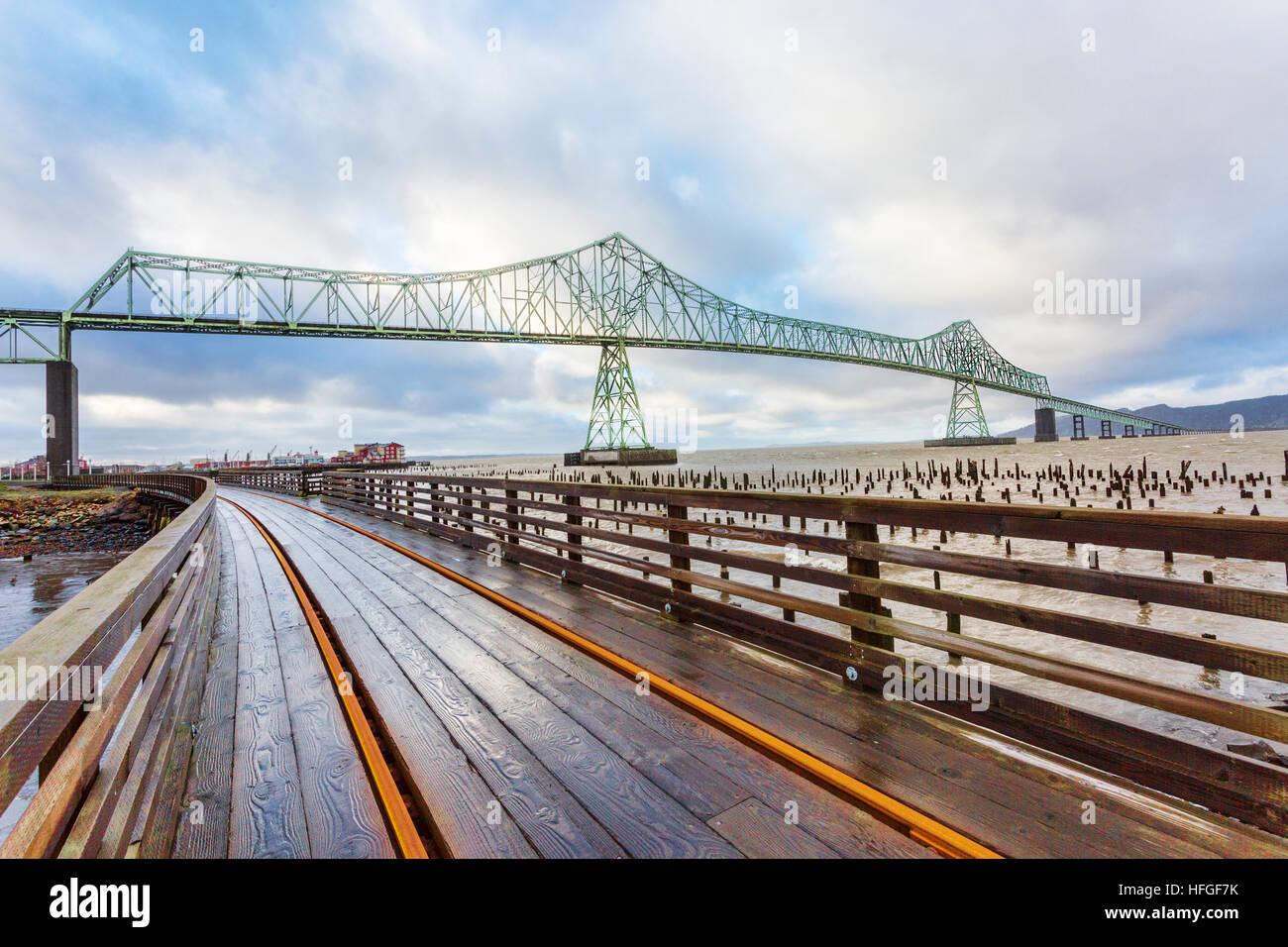 Trolley tracks, boardwalk, and Astoria-Megler Bridge, Columbia River, a steel girder continuous truss bridge spanning - Stock Image