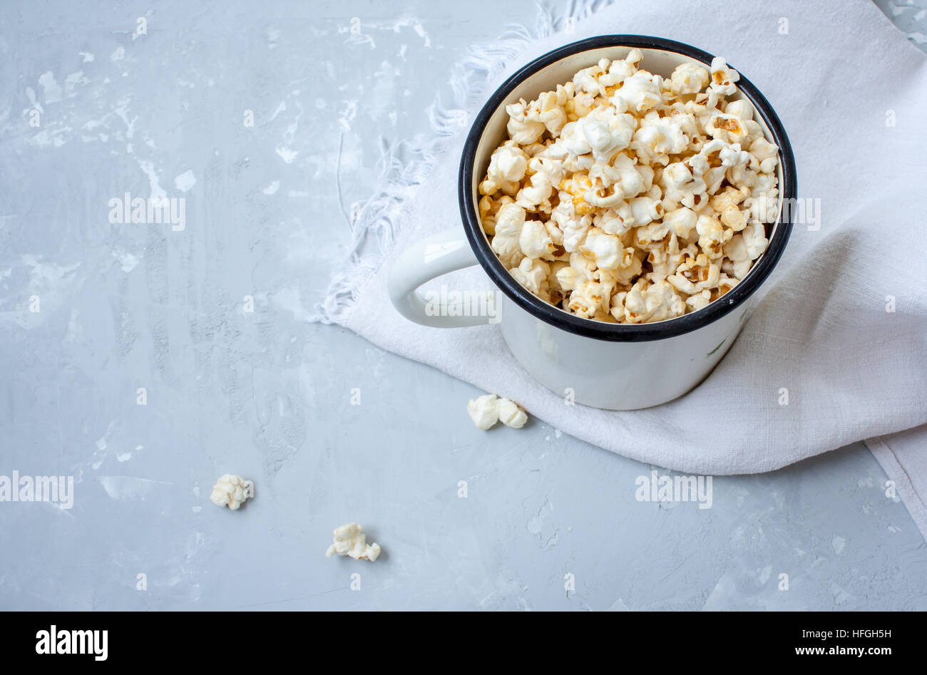 Sweet caramel popcorn in a large iron circle on the concrete gray background. Stock Photo