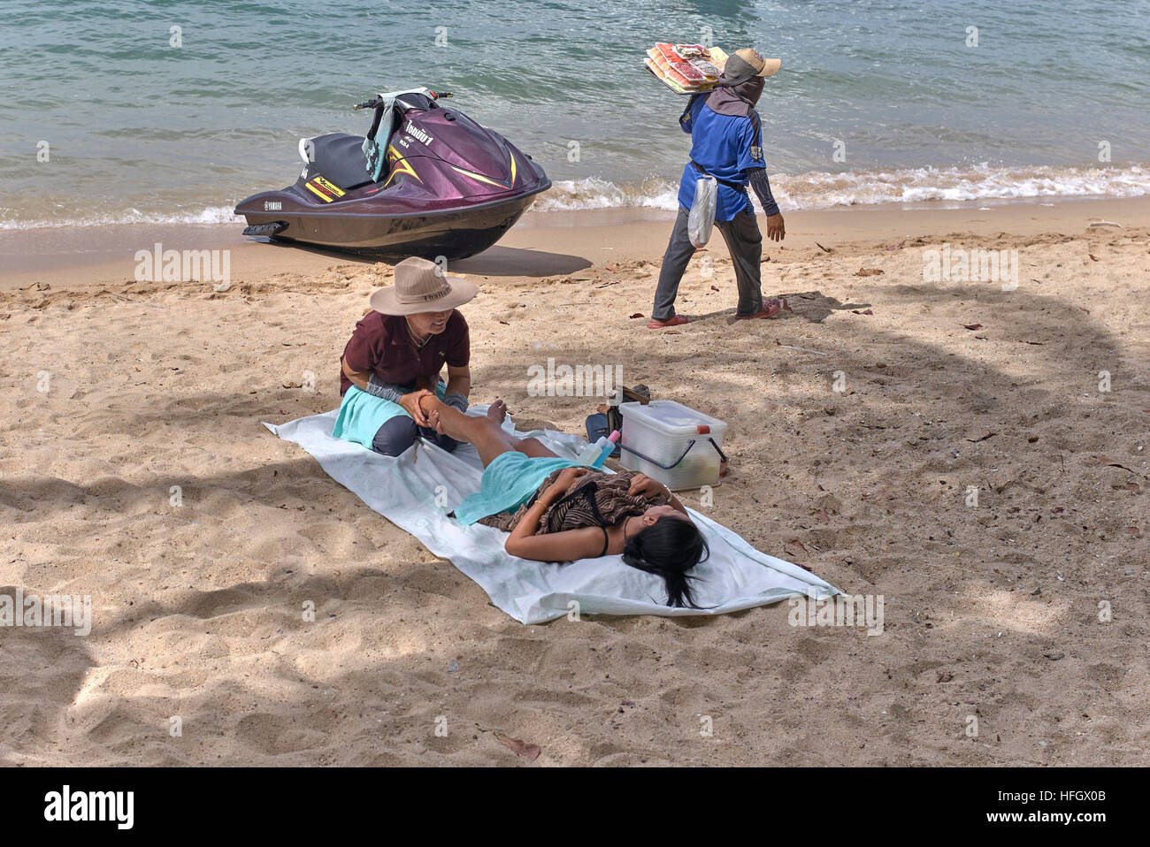 Female masseuse and female customer receiving a massage on the beach. Pattaya Thailand S. E. Asia - Stock Image