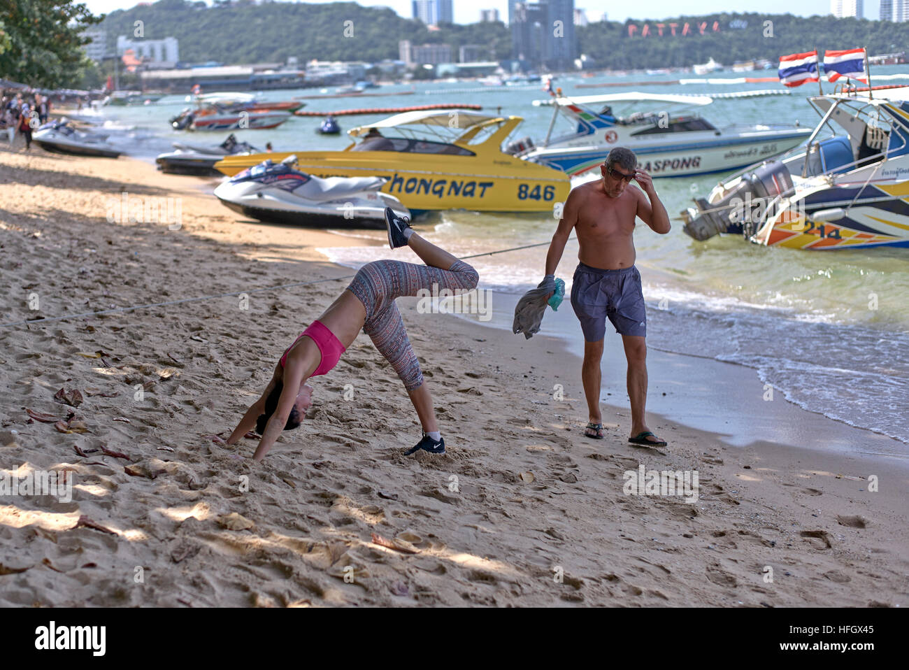 Female keep fit devotee exercising and working out on the beach at Pattaya Thailand S. E. Asia - Stock Image