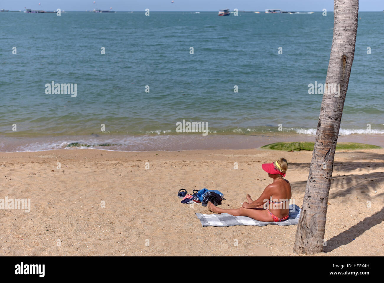 Bikini clad female sunbathing on a tropical beach. Pattaya Thailand S. E. Asia - Stock Image