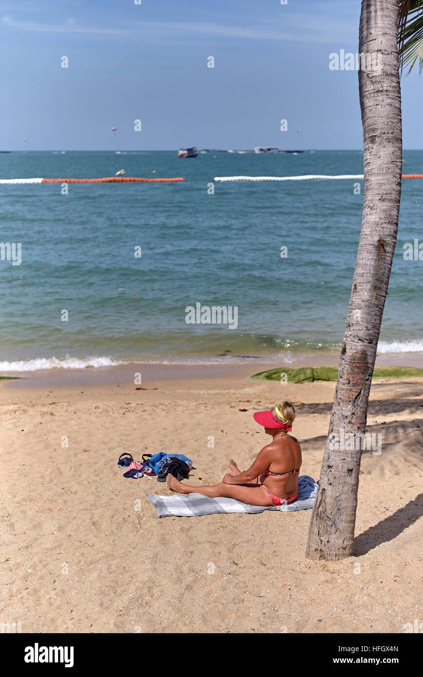 Bikini clad female sunbathing on a tropical beach. Pattaya Thailand S. E. Asia Stock Photo