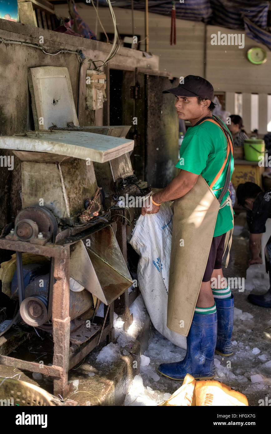 Operatives making crushed ice for local fish market food preservation. Thailand S. E. Asia - Stock Image