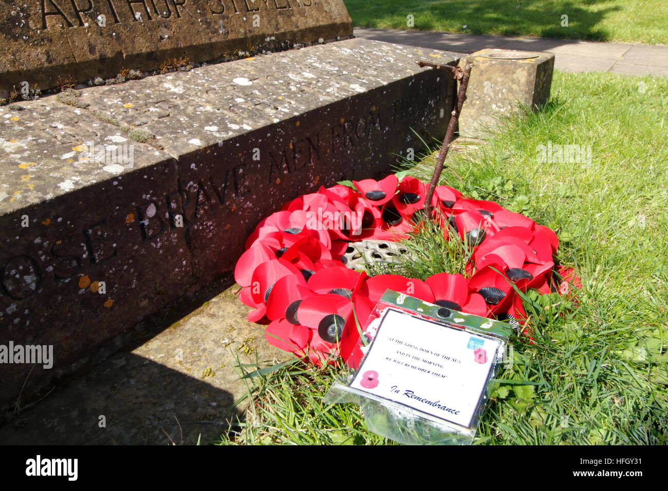 A wreath of poppies laid next to a memorial in a churchyard in Cropredy, Oxfordshire - Stock Image