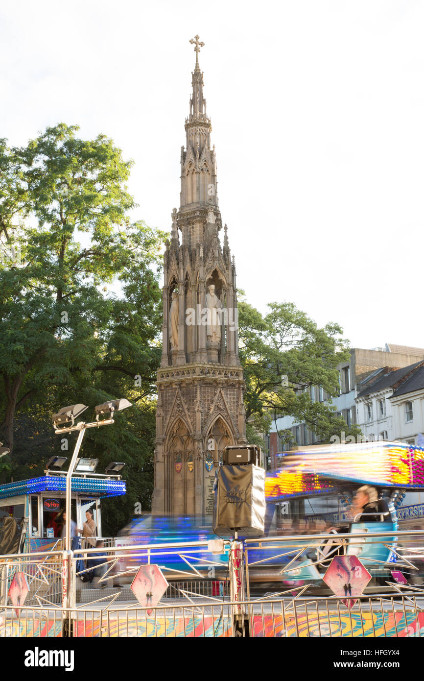 The Martyrs Memorial, Oxford, surrounded by the bustle of the annual autumn St Giles Fair with a variety of rides - Stock Image