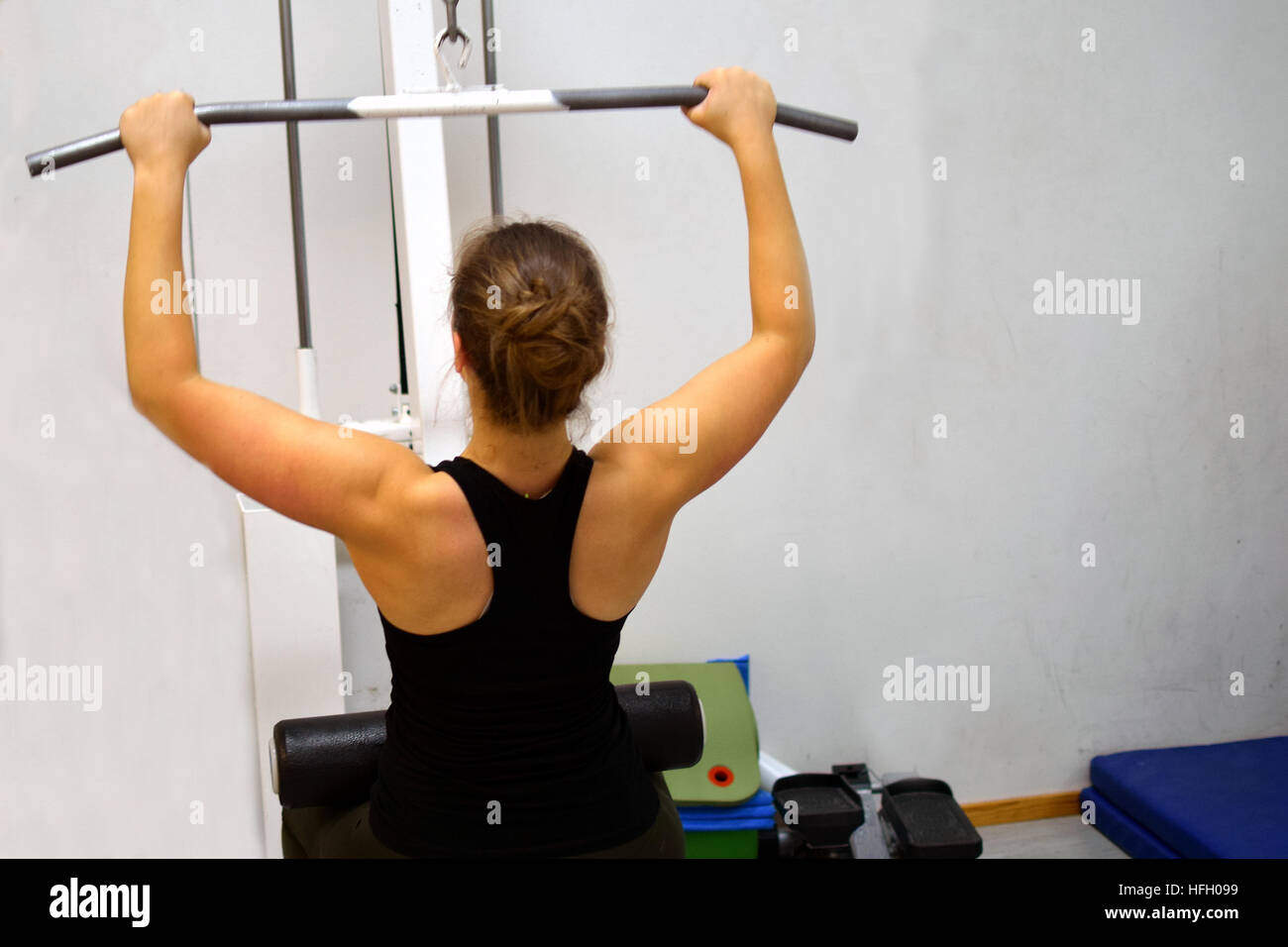 Woman at the gym. Working out her back muscles and arms with lat pulldown exercise machine. - Stock Image