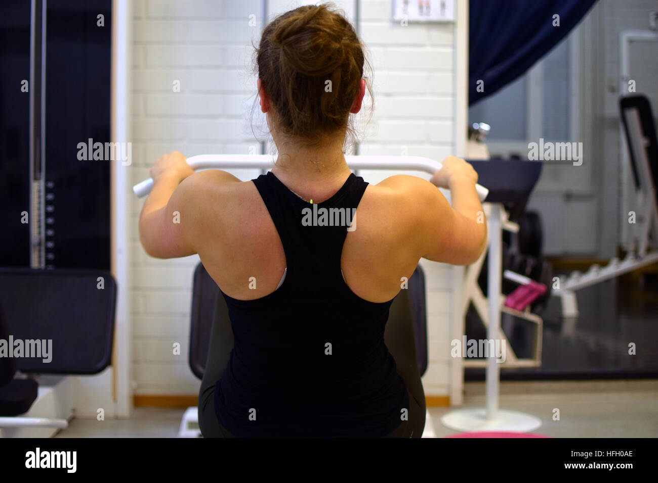 Woman working out her back muscles and arms with pulley at the gym. - Stock Image