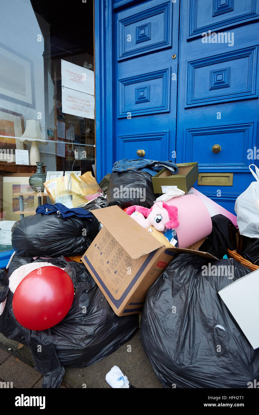 Bexley, UK, 31st December 2016. Old toys and clothes dumped in charity shop doorway after Christmas. The shop is - Stock Image