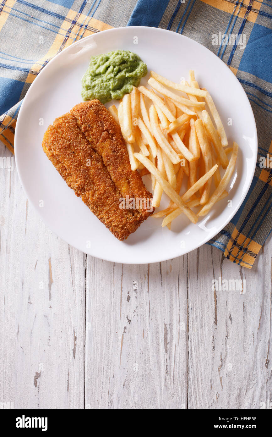 English food: fried fish in batter with chips and pea puree on a plate. vertical top view - Stock Image
