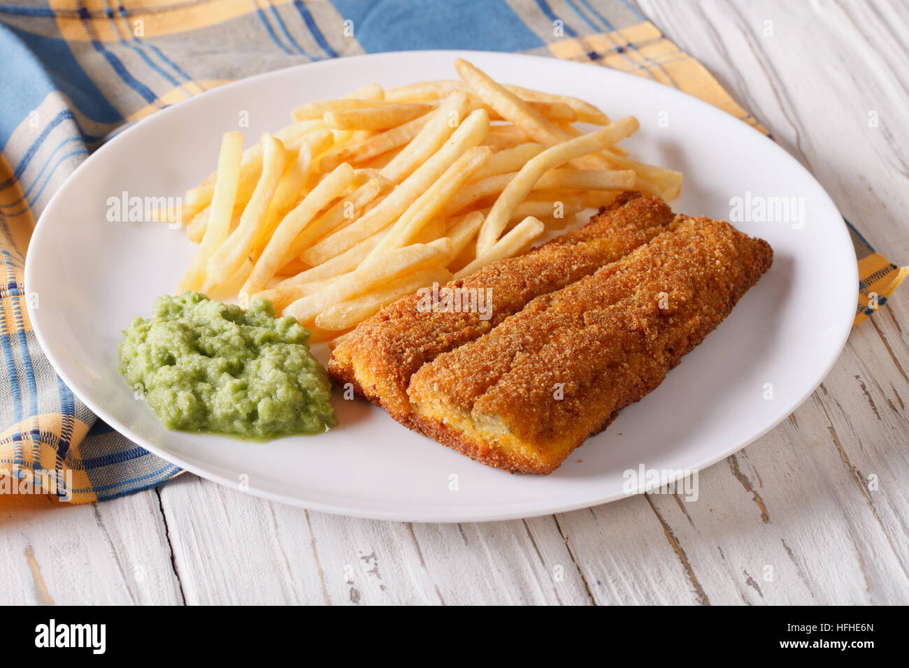 English food: fish in breadcrumbs with fried potatoes and pea puree on a plate. horizontal - Stock Image