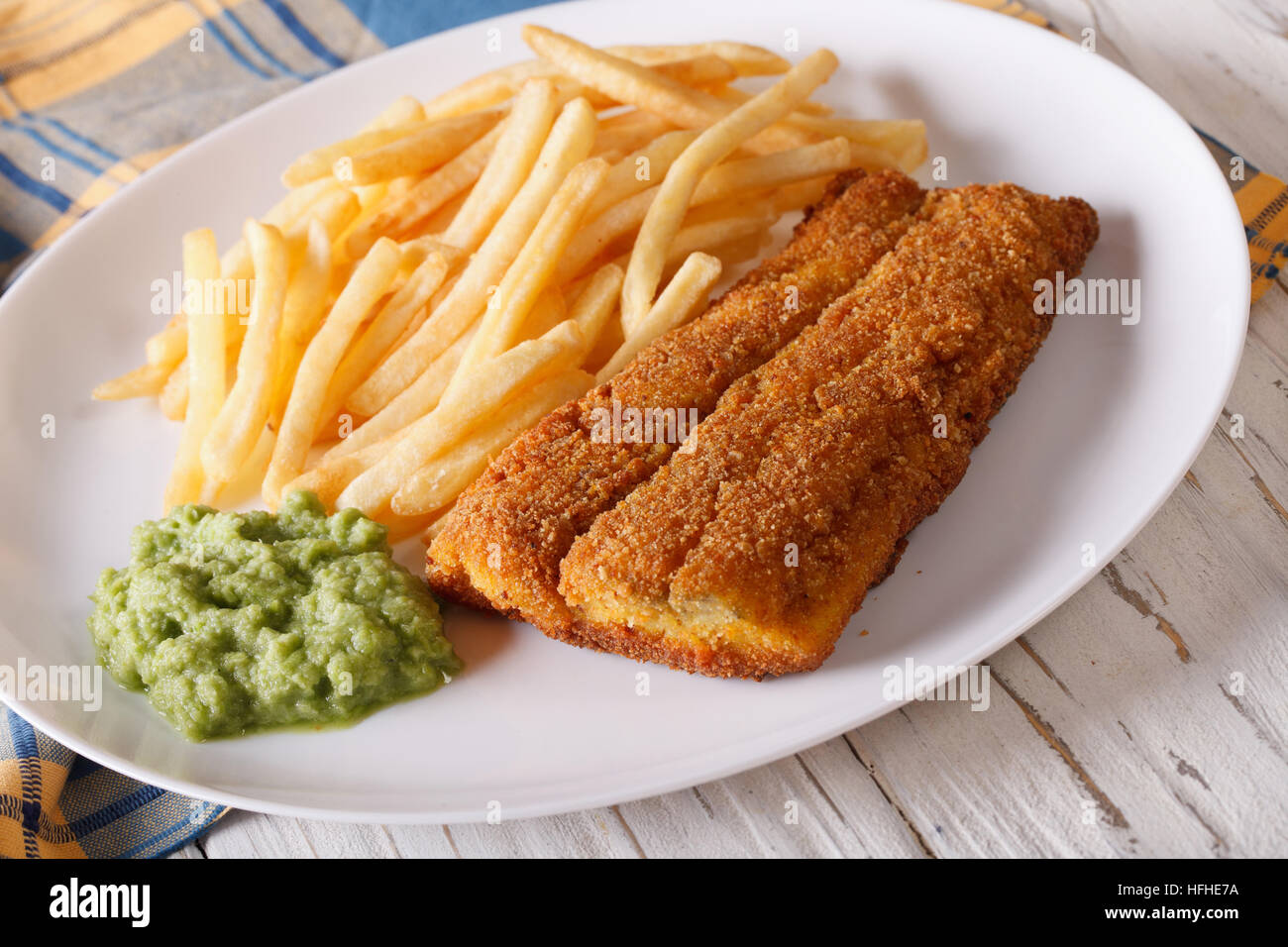 English food: fish in breadcrumbs with fried potatoes and pea puree close-up on a plate. horizontal - Stock Image
