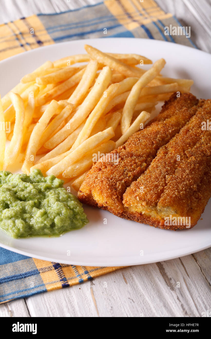 English food: fried fish fillets and chips and pea puree close-up on a plate. Vertical Stock Photo